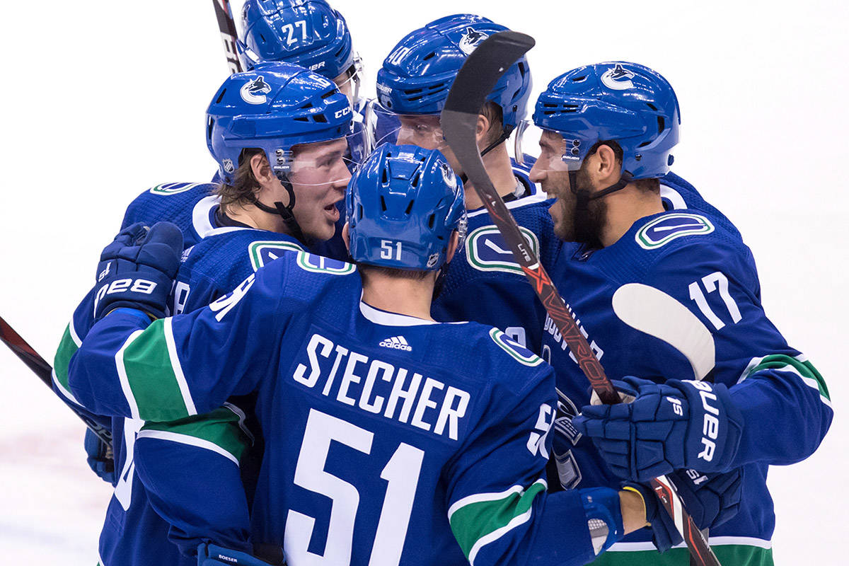 Vancouver Canucks' Brock Boeser, clockwise from left, Ben Hutton, Elias Pettersson, of Sweden, Josh Leivo and Troy Stecher celebrate Boeser's goal against the Philadelphia Flyers during the second period of an NHL hockey game in Vancouver, on Saturday December 15, 2018. THE CANADIAN PRESS/Darryl Dyck
