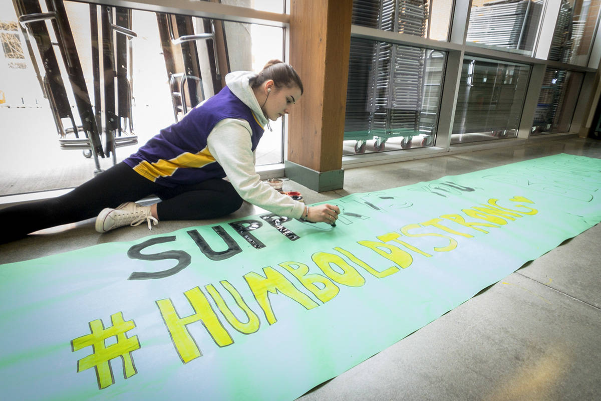 """I was at Penticton Secondary when I spotted this lone student off to one side of the common area, quietly painting a huge banner for a rally to show school support after the Humboldt tragedy. She looked up and smiled as I approached, then went back to work without a word while I made photos for a few minutes. There was a photo later at the rally with the whole school massed together, holding up the finished banner but this quiet young woman, working with Zen-like concentration, summed up the feeling even better."" (Steve Kidd/Penticton Western News)"