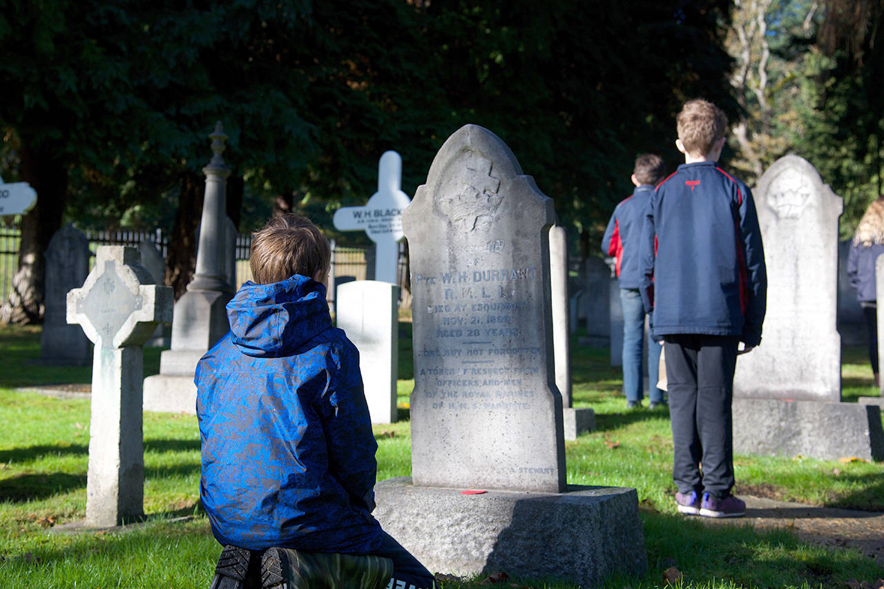 """Kids were all placing poppies at God's Acre Cemetery for Remembrance day. While they were all respectful, this one kid, Simon Lowe, was exceptionally pensive and sombre at each stone. He really took the time to read the names and reflect on people's lives, and I thought it was just such a neat representation of the depth and compassion kids can have. I even approached him to see if I could ask him about his thoughts, and he politely told me I could talk to him after he was done."" (Nicole Crescenzi/News Staff)"