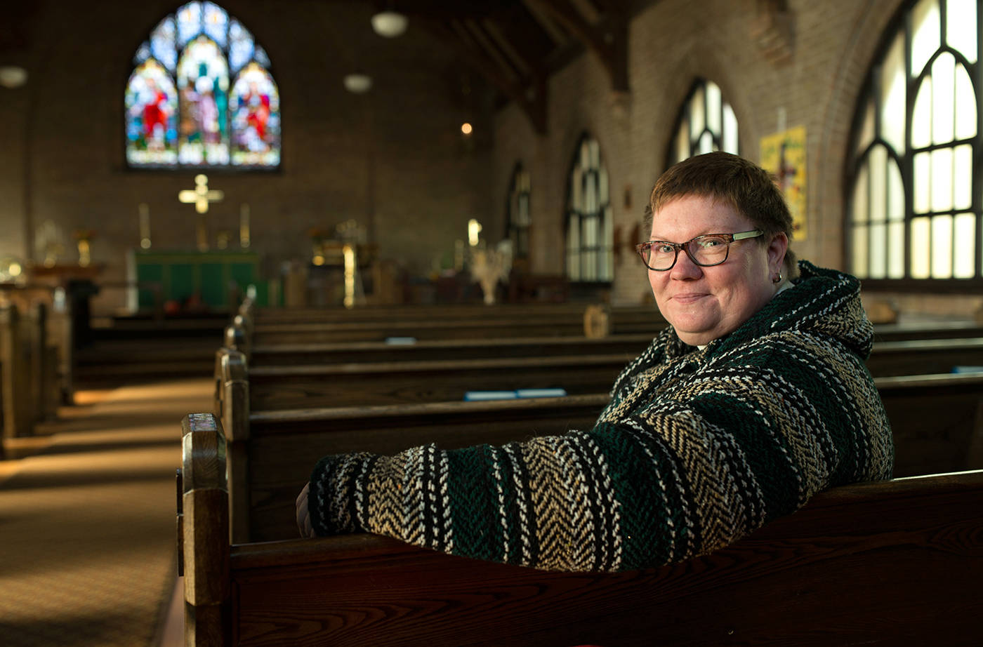 """Reverend Andrea Brennan is one of the most recognizable faces around town for one particular reason – she's always smiling. For almost three years she has served as the minister of the Christ Church Anglican in Fernie. Behind the everlasting smile is a person confident in what they believe in and not afraid to challenge the status quo. Aside from breaking the stereotype by being a female minister, Brennan is also openly queer. She is also serving at a time when her denomination is considering marrying same-sex couples."" (Phil McLachlan/The Fernie Free Press)"