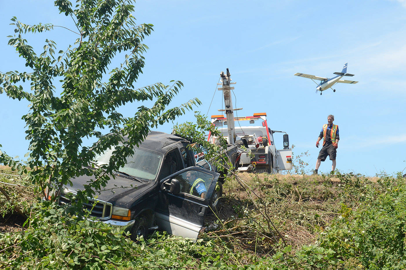"""This is the aftermath of a prolific offender stealing a vehicle in Abbotsford, racing to Chilliwack, and rolling the pickup on this embankment. It took a team of tow-truck drivers to remove the truck and its trailer from the blackberry bushes. This was taken from below as the truck was being pulled up to the road and as a plane serendipitously flew overhead giving the photo a little more visual interest."" (Paul Henderson/Chilliwack Progress)"