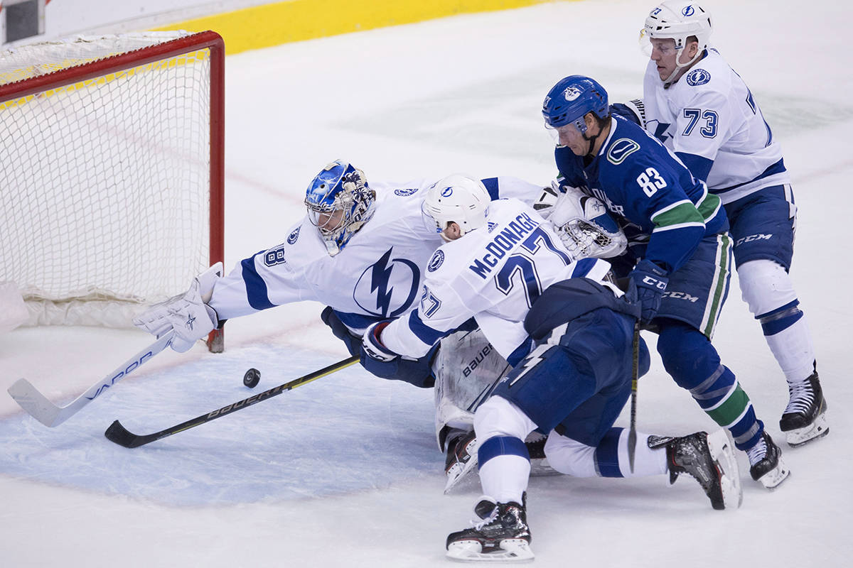 Tampa Bay Lightning goaltender Andrei Vasilevskiy (88) tries to stop Vancouver Canucks defenceman Christopher Tanev's goal as Tampa Bay Lightning defenceman Ryan McDonagh (27), Tampa Bay Lightning left wing Adam Erne (73) and Vancouver Canucks centre Jay Beagle (83) look on during third period NHL action at Rogers Arena in Vancouver, Tuesday, Dec. 18, 2018. THE CANADIAN PRESS/Jonathan Hayward