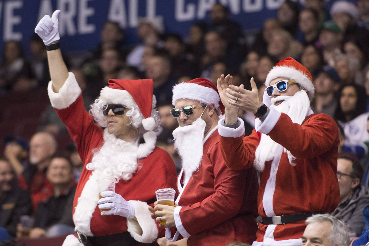 Hockey fans dressed as Santa Claus cheer during the first period of NHL action between the Tamp Bay Lightning and the Vancouver Canucks at Rogers Arena in Vancouver, Tuesday, Dec. 18, 2018. THE CANADIAN PRESS/Jonathan Hayward