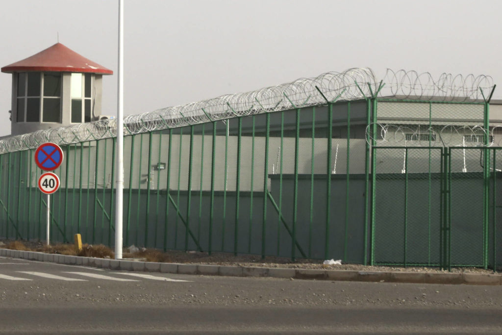 In this Monday, Dec. 3, 2018, photo, a guard tower and barbed wire fences are seen around a facility in the Kunshan Industrial Park in Artux in western China's Xinjiang region. (AP Photo/Ng Han Guan)