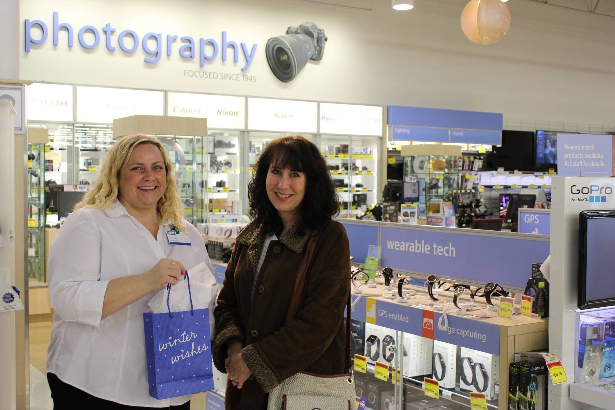 Angeline Haslett (right) poses with store manager Lillian Fast at a London Drugs store in Chilliwack after she was named the Amateur Photographer of the Year. (Photo by Kieran O'Connor/Black Press Media)