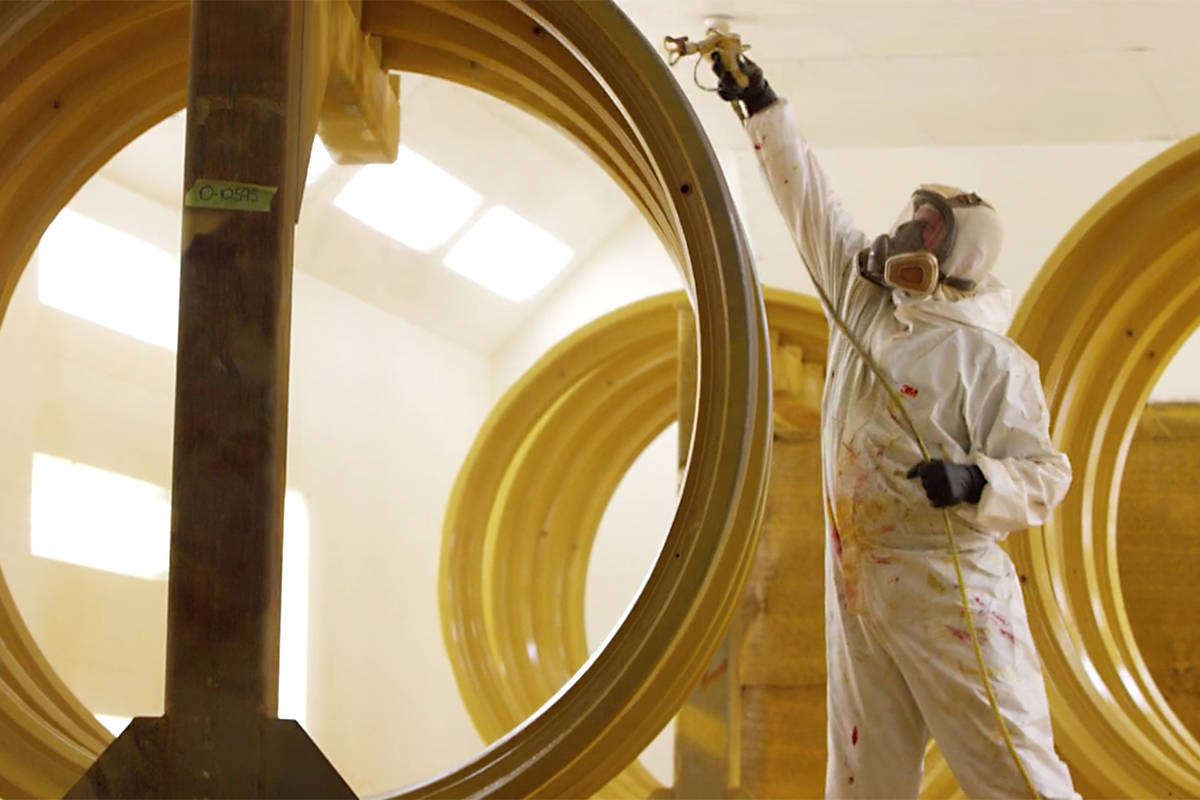 A Rimex employee applies paint to some giant-sized wheel assemblies.