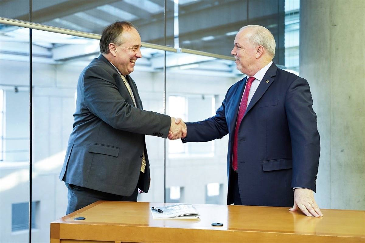 B.C. Green leader Andrew Weaver and Premier John Horgan autograph a copy of the 'CleanBC' plan to reduce greenhouse gas emissions over the next two decades, Vancouver cabinet office, Dec. 5, 2018. (B.C. government)