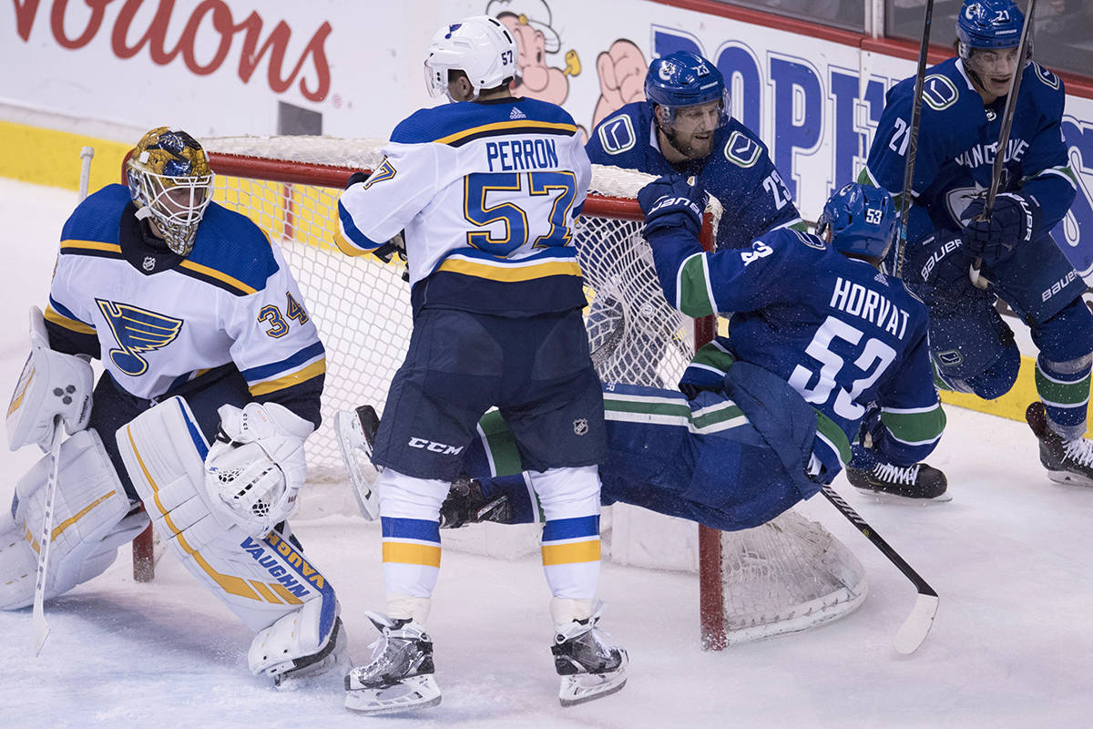 St. Louis Blues goaltender Jake Allen (34) looks on as Vancouver Canucks center Bo Horvat (53) gets sent into the goalpost by St. Louis Blues left wing David Perron (57) during second period NHL action at Rogers Arena in Vancouver, Thursday, Dec. 20, 2018. THE CANADIAN PRESS/Jonathan Hayward
