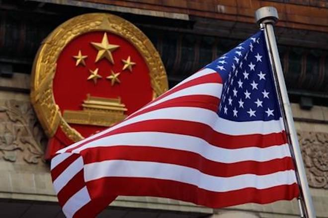 FILE - In this Nov. 9, 2017, file photo, an American flag is flown next to the Chinese national emblem during a welcome ceremony at the Great Hall of the People in Beijing. (AP Photo/Andy Wong, File)