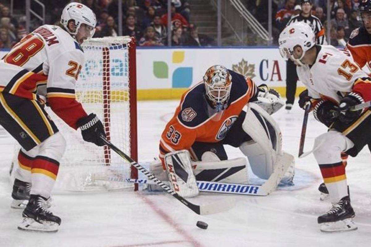 Calgary Flames ' Elias Lindholm (28) is stopped by Edmonton Oilers' goalie Cam Talbot (33) as Johnny Gaudreau (13) looks for the loose puck during third period NHL preseason action in Edmonton on Saturday September 29, 2018. (THE CANADIAN PRESS/Jason Franson)