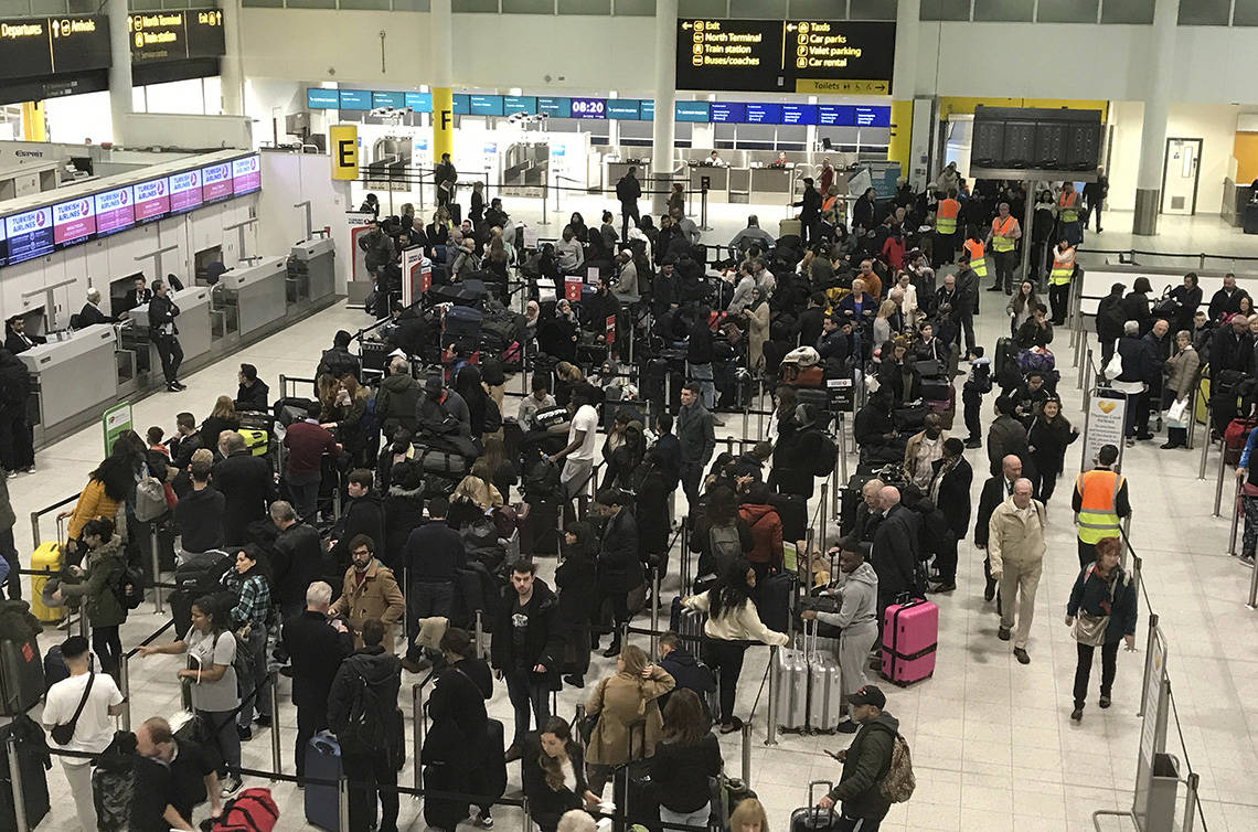 Passengers wait to check in at Gatwick Airport in England, Friday, Dec. 21, 2018. Flights resumed at London's Gatwick Airport on Friday morning after drones sparked the shutdown of the airfield for more than 24 hours, leaving tens of thousands of passengers stranded or delayed during the busy holiday season. (AP Photo/Kirsty Wigglesworth)