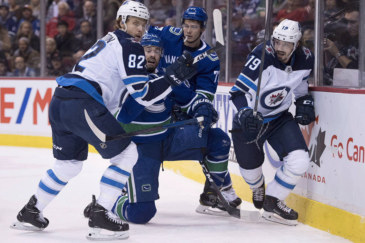 Vancouver Canucks defenceman Erik Gudbranson (44) fights for control of the puck with Winnipeg Jets center Mason Appleton (82) and Winnipeg Jets left wing Nic Petan (19) during first period NHL action at Rogers Arena in Vancouver, Saturday, Dec. 22, 2018. THE CANADIAN PRESS/Jonathan Hayward