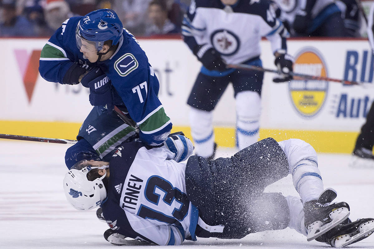 Winnipeg Jets left wing Brandon Tanev (13) fights for control of the puck with Vancouver Canucks right wing Nikolay Goldobin (77) during first period NHL action at Rogers Arena in Vancouver, Saturday, Dec. 22, 2018. THE CANADIAN PRESS/Jonathan Hayward