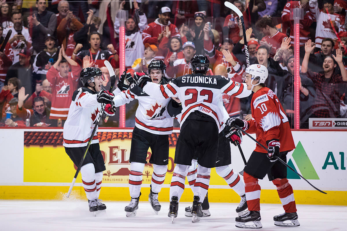 Canada's Jared McIsaac, from left to right, Shane Bowers, MacKenzie Entwistle, back right, and Jack Studnicka celebrate Entwistle's goal as Switzerland's Yannick Bruschweiler (10) skates to the bench during second period IIHF world junior hockey championship action in Vancouver, on Thursday December 27, 2018. THE CANADIAN PRESS/Darryl Dyck