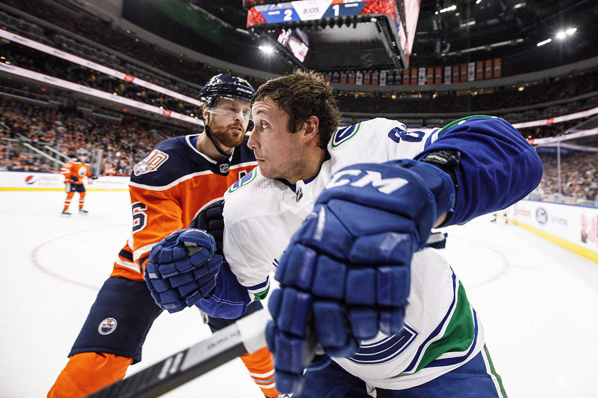 Vancouver Canucks' Jay Beagle (83) and Edmonton Oilers' Adam Larsson (6) battle for the puck during first period NHL action in Edmonton, Alta., on Thursday December 27, 2018. THE CANADIAN PRESS/Jason Franson