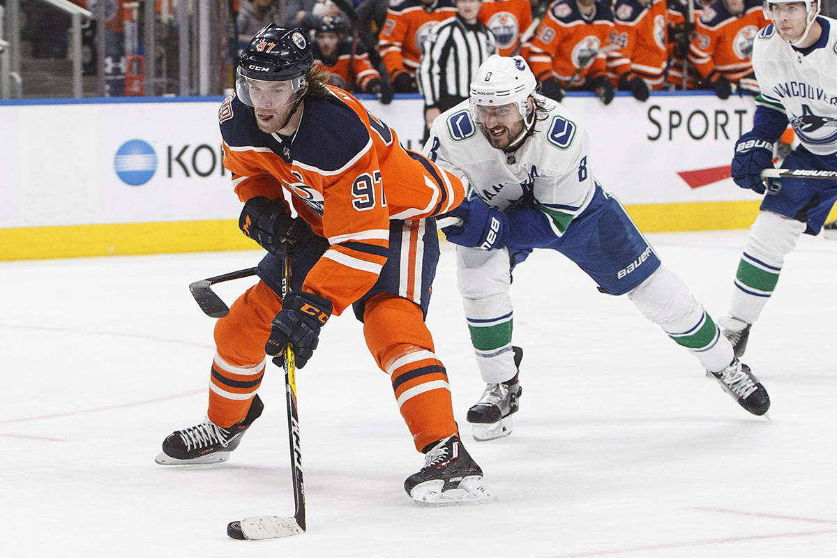 Vancouver Canucks' Chris Tanev (8) chases Edmonton Oilers' Connor McDavid (97) during second period NHL action in Edmonton, Alta., on Thursday December 27, 2018. THE CANADIAN PRESS/Jason Franson