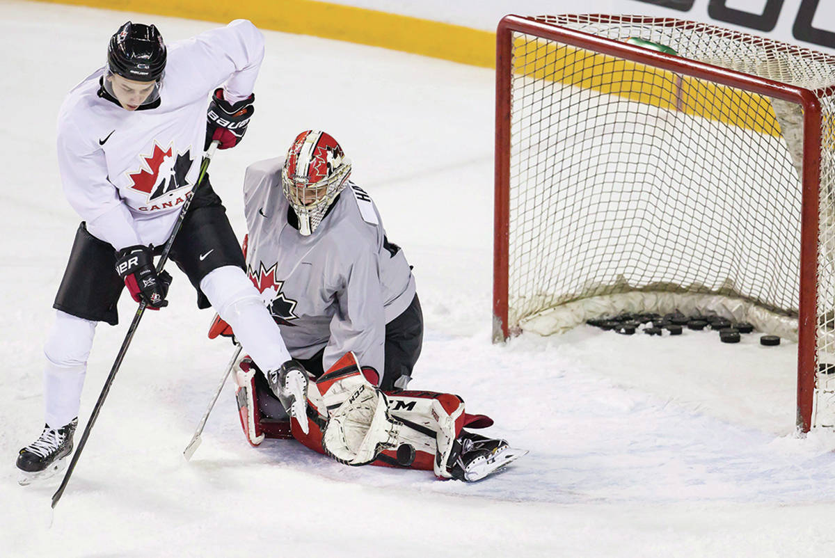 Canadian national junior team goaltending prospect Carter Hart, right, makes a pad save while being screened by forward Cody Glass on the first day of selection camp for the 2018 World Junior Hockey Championship in St.Catharines, Ont., Tuesday, December 12, 2017. (Aaron Lynett/The Canadian Press)