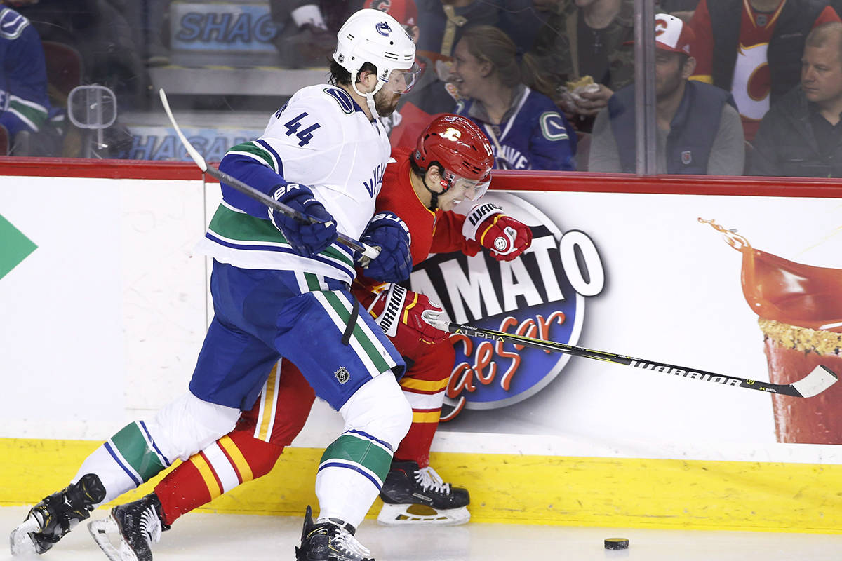 Vancouver Canucks' Erik Gudbranson, left, battles for the puck with Calgary Flames' Johnny Gaudreau during first period NHL action in Calgary, Saturday, Dec. 29, 2018. THE CANADIAN PRESS/Larry MacDougal