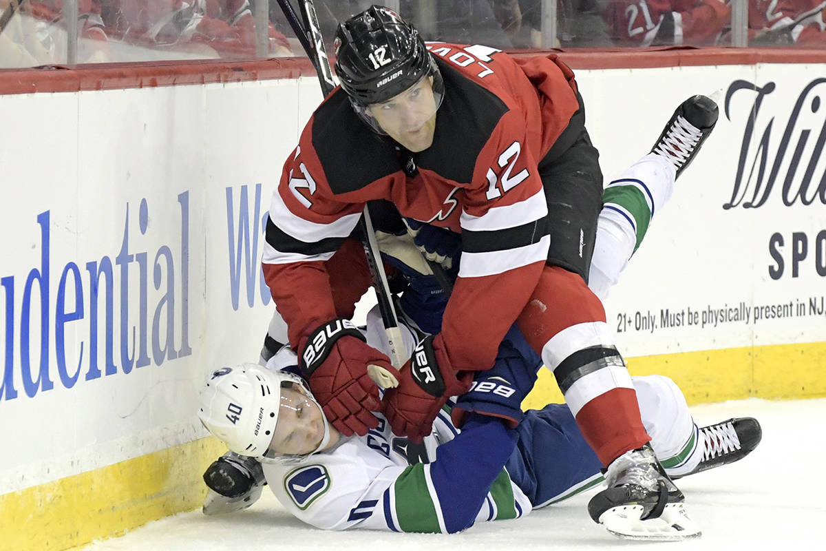 New Jersey Devils defenceman Ben Lovejoy (12) checks Vancouver Canucks centre Elias Pettersson (40) during the first period of an NHL hockey game Monday, Dec. 31, 2018, in Newark, N.J. (AP Photo/Bill Kostroun)