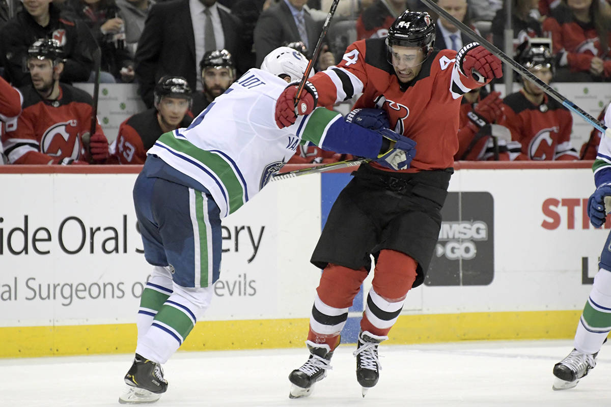 Vancouver Canucks defenceman Derrick Pouliot (5) checks New Jersey Devils left wing Miles Wood (44) during the second period of an NHL hockey game Monday, Dec. 31, 2018, in Newark, N.J. (AP Photo/Bill Kostroun)