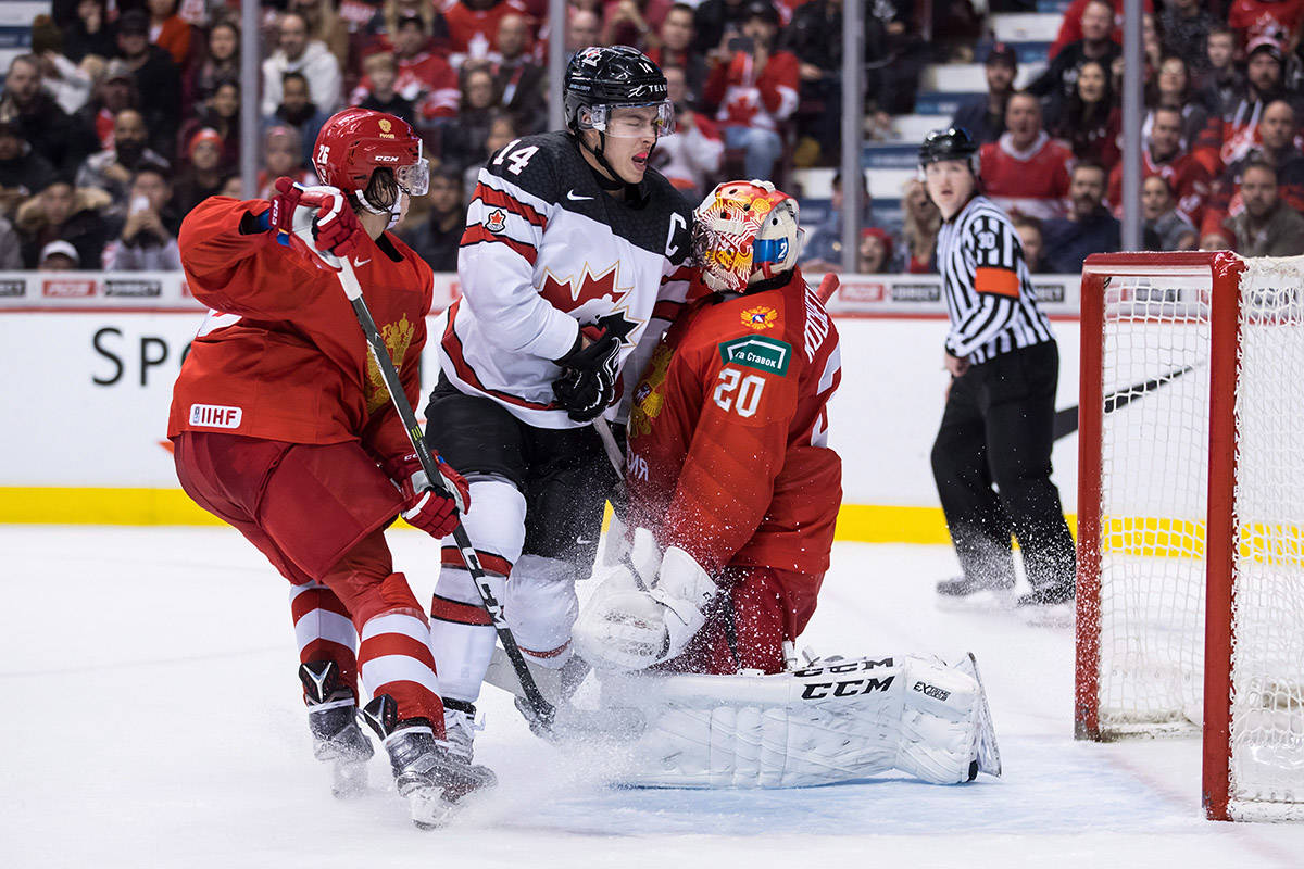 Canada's Maxime Comtois (14) bumps into Russia goalie Pyotr Kochetkov (20) after the puck deflected wide of the goal while Russia's Alexander Romanov, left, defends during second period IIHF world junior hockey championship action in Vancouver on Monday, Dec. 31, 2018. THE CANADIAN PRESS/Darryl Dyck