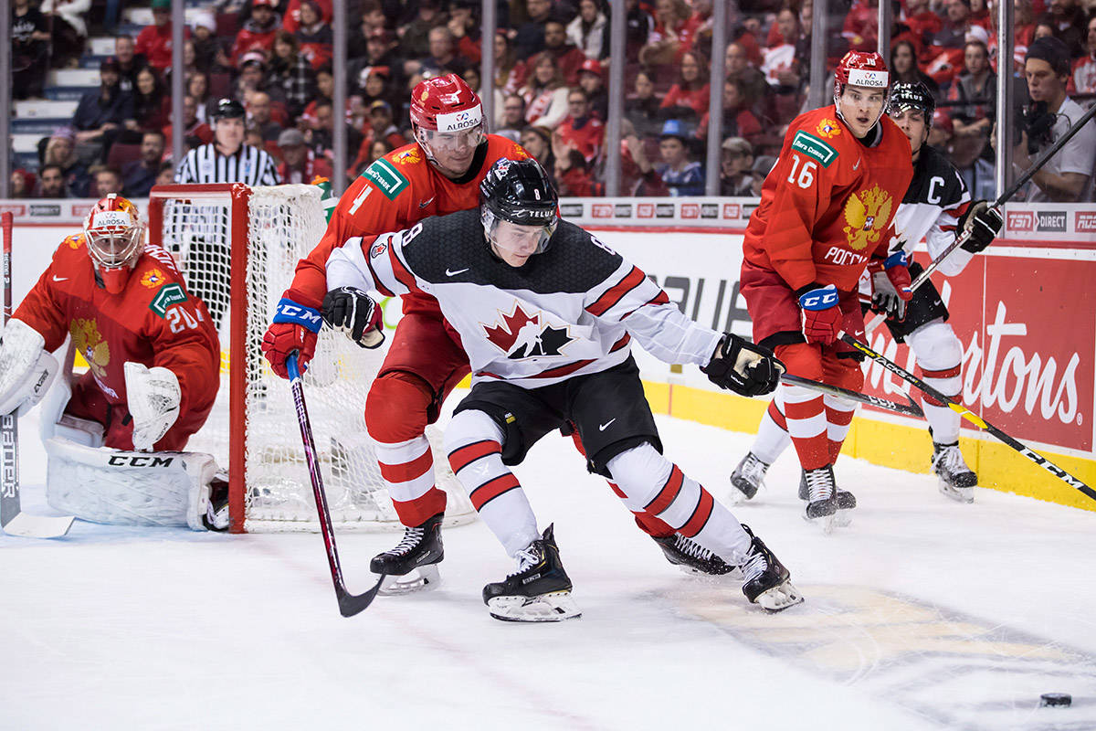 Canada's Cody Glass (8) reaches for the puck while being checked by Russia's Alexander Alexeyev during second period IIHF world junior hockey championship action in Vancouver on Monday, Dec. 31, 2018. THE CANADIAN PRESS/Darryl Dyck