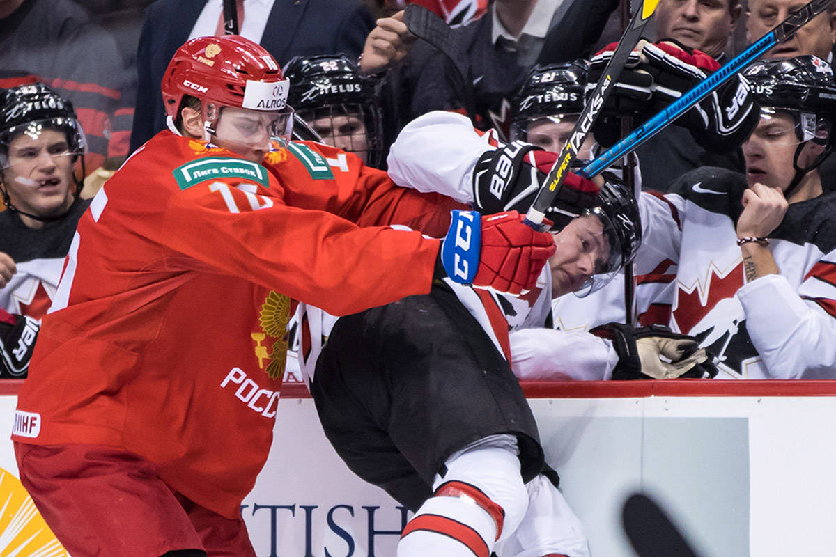 Russia's Pavel Shen, left, checks Canada's Barrett Hayton during second period IIHF world junior hockey championship action in Vancouver on Monday, Dec. 31, 2018. THE CANADIAN PRESS/Darryl Dyck