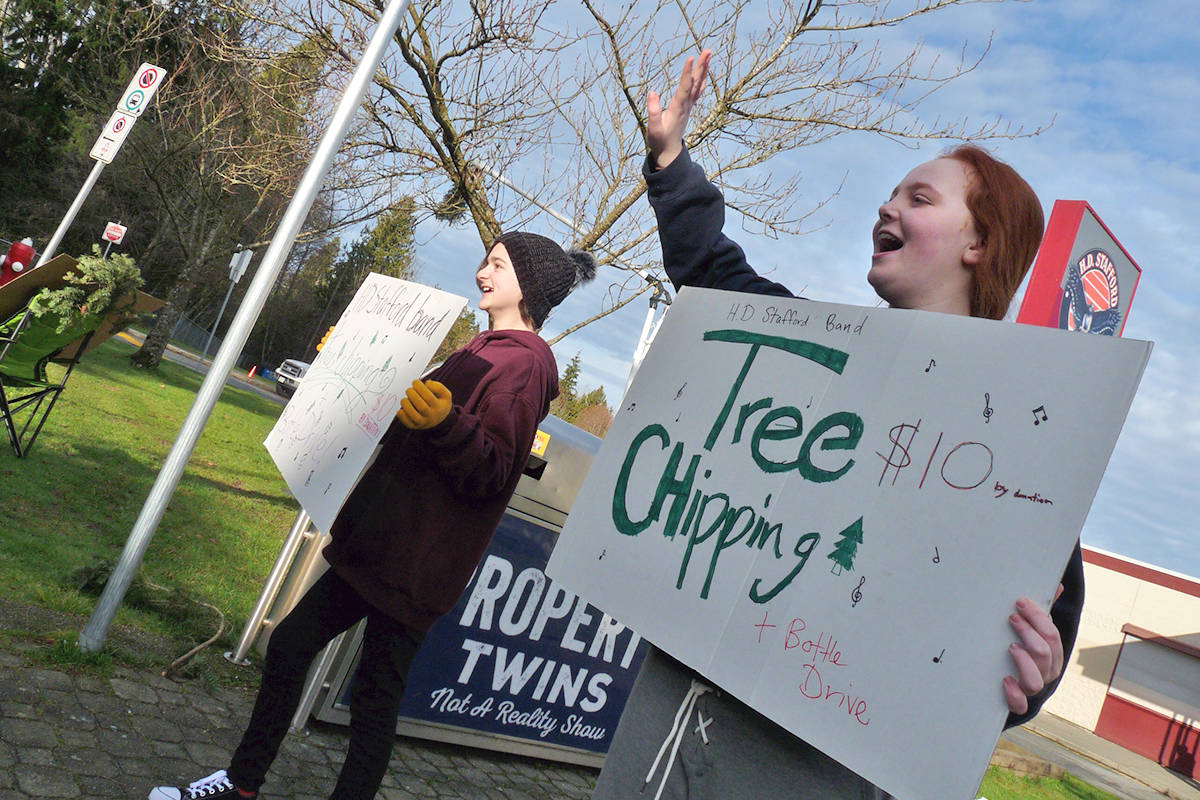 Emily Foster and Zoey Petersen were drumming up business at H.D. Stafford. Money from the tree chipping helps the school band. Black Press Photo