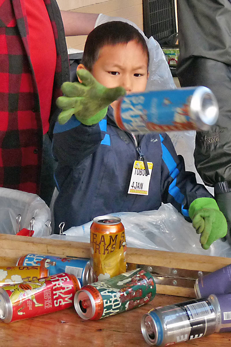Matthew, 7, pitches a can in the right bag at Walnut Grove. Black Press photo