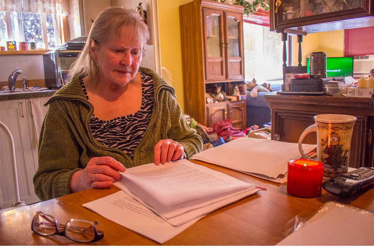 Myers thumbs through documents that tell her she must leave her home by May 31, 2019. (Liam Harrap/Revelstoke Review)
