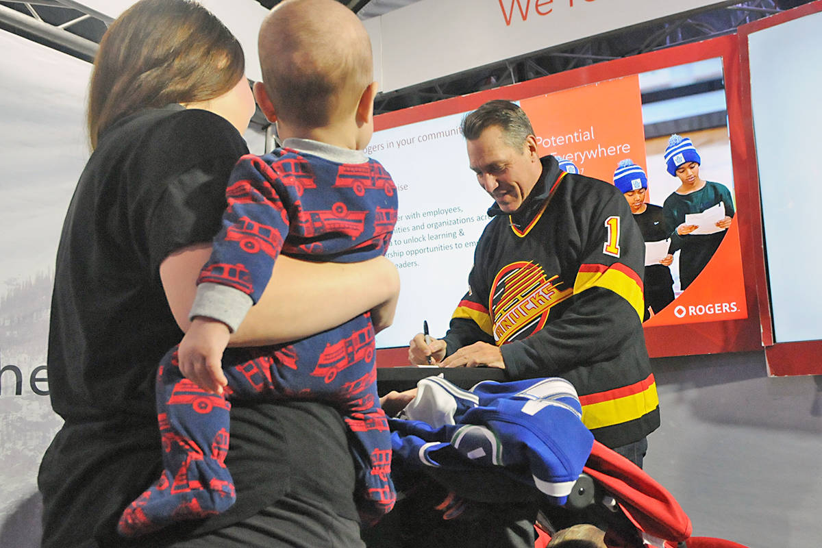 Kirk Mclean signs an autograph at the Rogers Hometown Hockey tour in Langley City. Black Press photo.