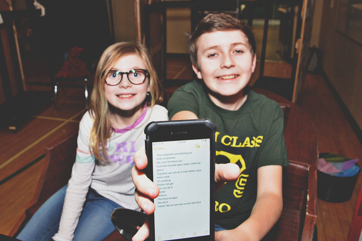 Ava Stumph and Markus Blessing portray the Potts children. Markus, Grade 9, has his script on his cellphone so he can run lines anytime. (Heather Colpitts/Langley Advance)