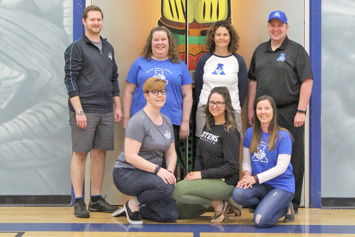 Katie Caines, Laura MacDonald, Wendy Potter, (back row) Zach Dahl, Shawna Urban, Kim Haber, and Jeremy Lyndon are ACSS students who went on to work at the school. (ACSS photo)