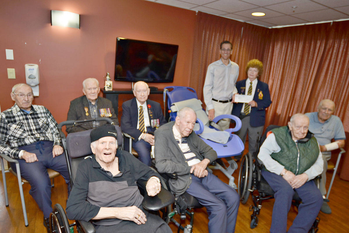 Langley Lodge is home to veterans such as (front row left to right) Dennis Horgan, David Berregar, David Penman, and Bob Baird, and (back row) George Clampitt, Tom Brown, John Paley. They and other lodge residents benefit from Legion donations. Langley Care Foundation fundraising director Patrick Matiowski recently received a donation of $20,750 from Wilma McEwan, with the Langley Legion Branch 21. (Heather Colpitts/Langley Advance)