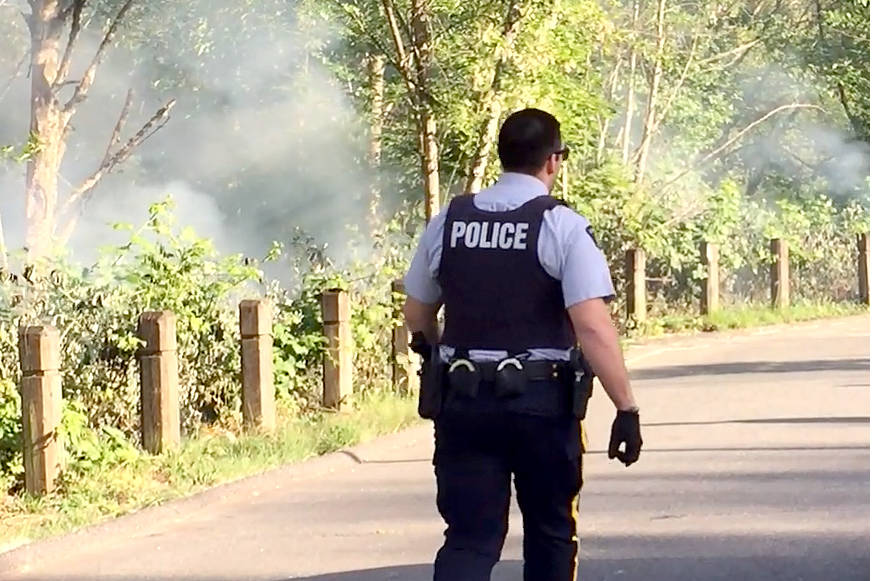 An RCMP officer at a small fire that appears to have been deliberately set in Langley City earlier this week. (Roxanne Hooper/Langley Advance)
