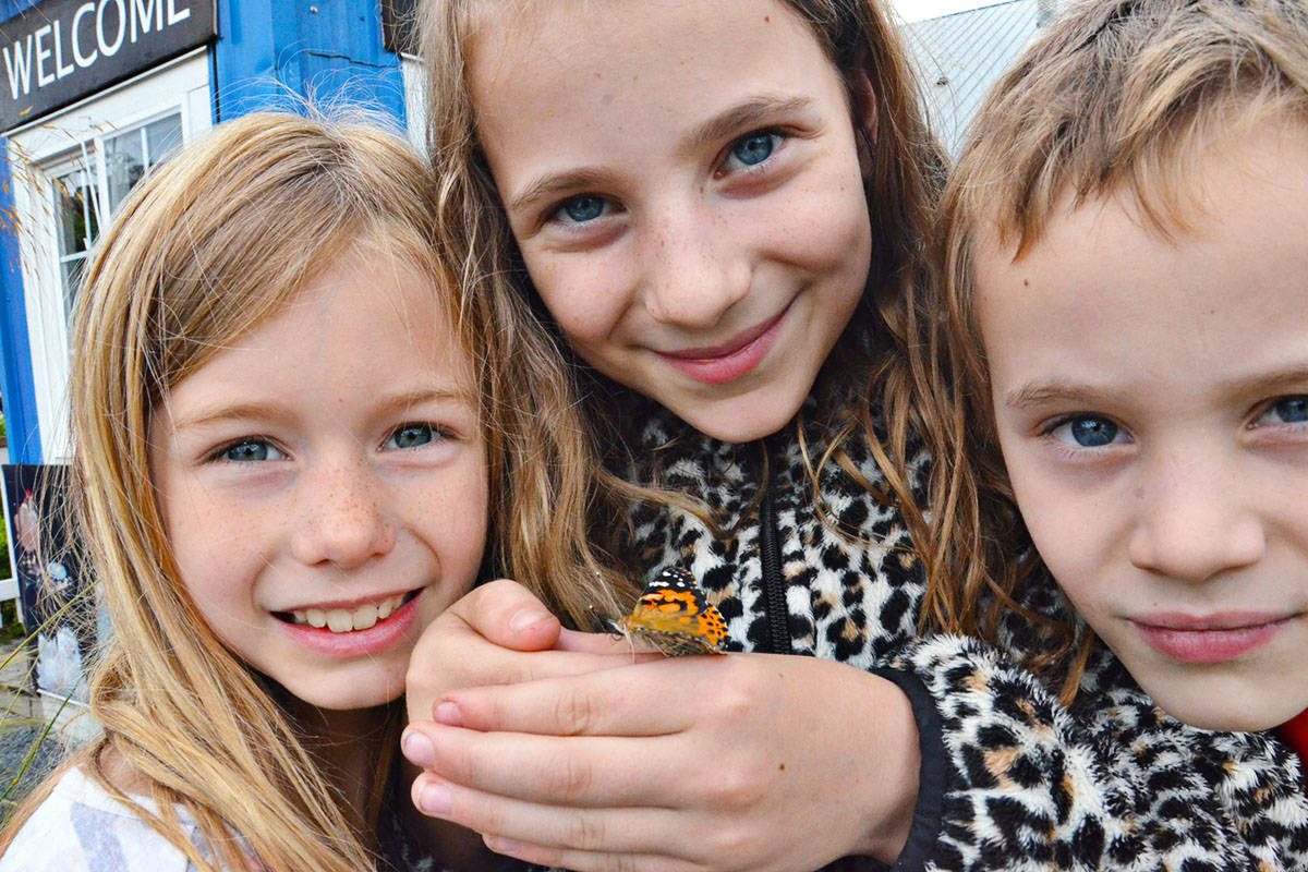 Maya Bradley, Meghan Pasha and Daniel Pasha had one of the butterflies stop by for a quick visit. (Heather Colpitts/Langley Advance)