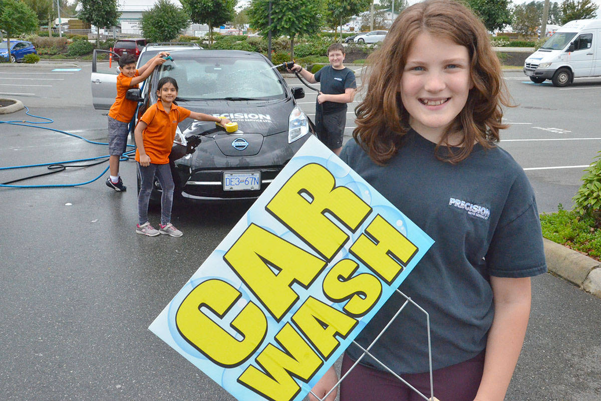 Noah and Leima Eshaghzey, and Michael and Megan Waddle helped at the charity car wash at Precision Auto on Saturday. (Heather Colpitts/Langley Advance)
