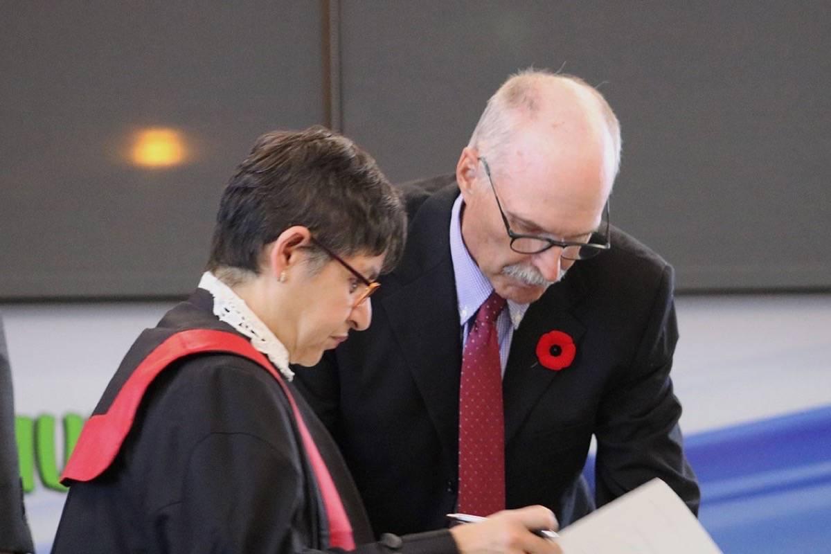 Trustee Rod Ross signs his oath with Honourable Judge Rita Bowry. Miranda Fatur Black Press