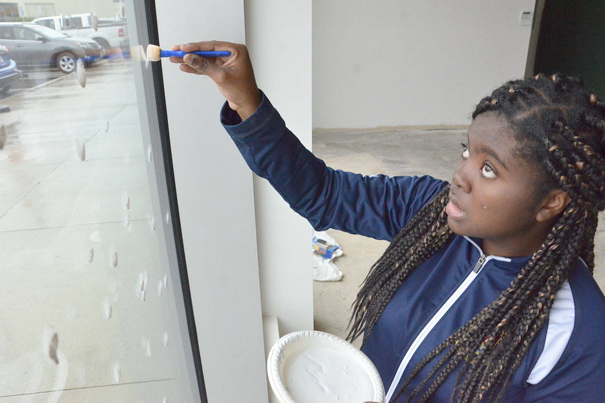 Jade Wright put her artistic talents to work helping paint festive scenes on the windows at the Langley Christmas Bureau. Wright was one of a handful of Vanguard Secondary students who helped the bureau set up shop for the season. (Heather Colpitts/Black Press)
