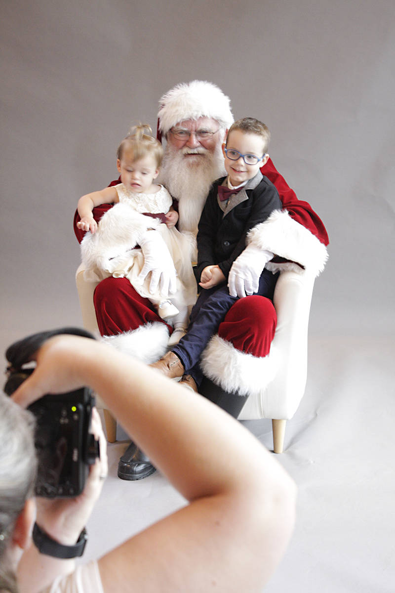 Siblings Karra and Eli Pink get their picture taken with the Jolly Old Elf at the Breakfast With Santa fundraiser for Langley Child Development Services. Black Press