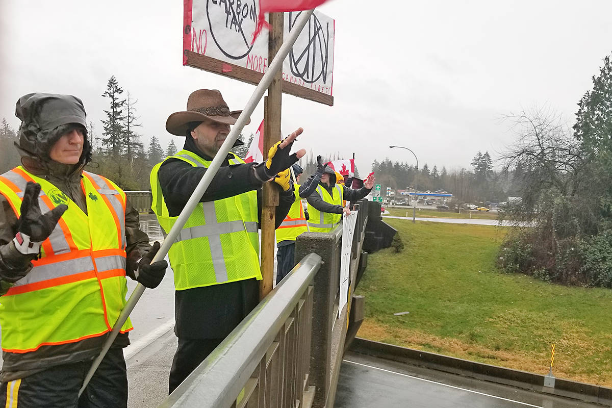 Protester Terry Harder (second from left) waves to traffic at a Saturday 'yellow vest' protest on the 232 Street overpass in Langley. Black Press photo