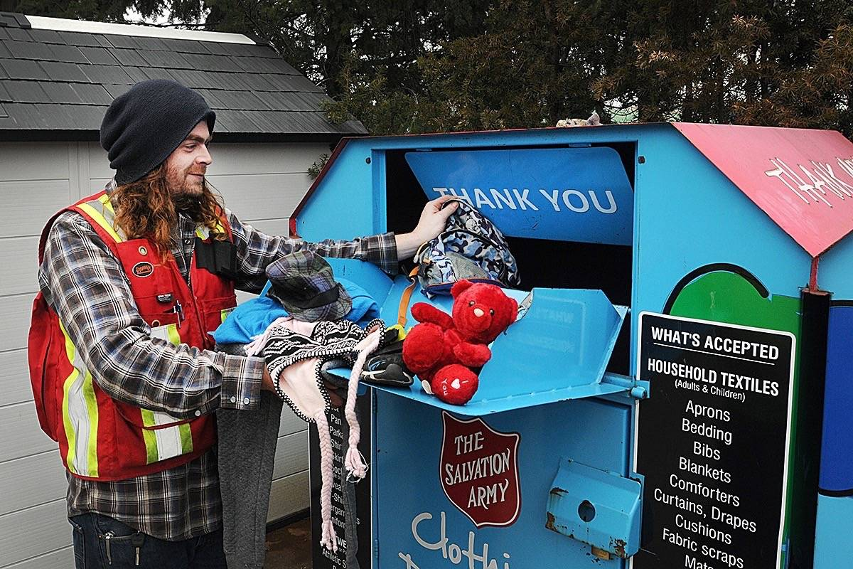 Sebastian Fralic, supervisor at Ridge Meadows Recycling puts donated items of clothing, shoes and a stuffed animal into a Salvation Army bin at the depot Thursday morning. The bins are behind locked gate with security during off hours, but don't have a chute and are easy to get out of if someone were to climb in. (Colleen Flanagan/THE NEWS)