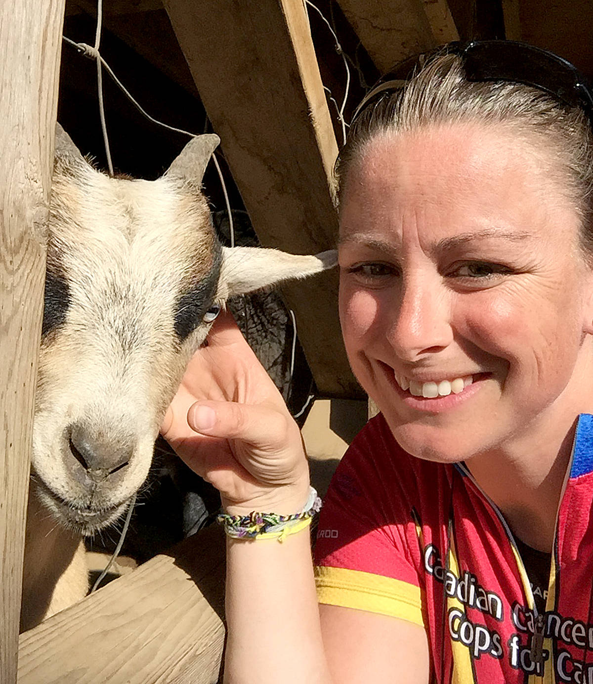 Langley Mountie Rochelle Carr was found playing with the goats during a visit to Mann Farms in her hometown of Abbotsford on Tuesday. (Special to the Langley Advance)