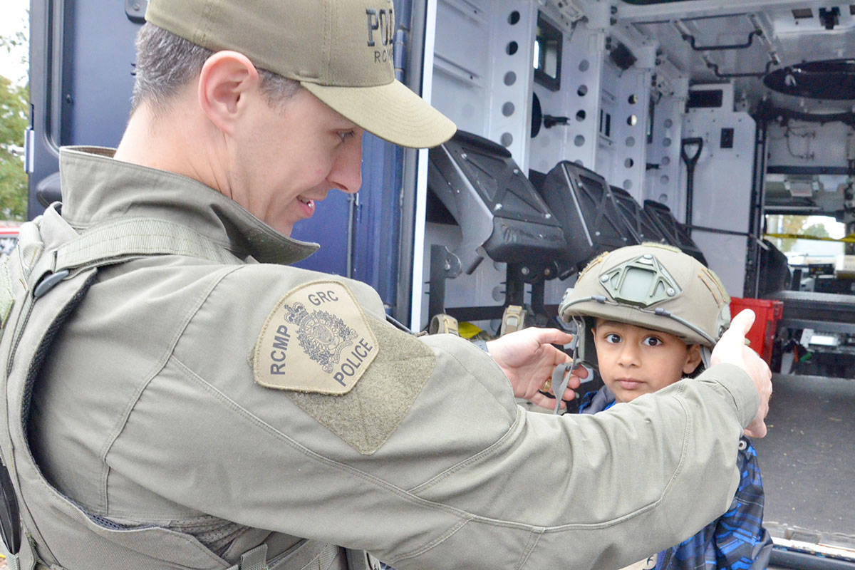 Const. Winslow helped five-year-old Arjun Mann try on a helmet used by the Emergency Response Team at the Langley Emergency Preparedness Fair on Saturday. People could check out the specialty vehicles and meet emergency responders. (Heather Colpitts/Langley Advance)