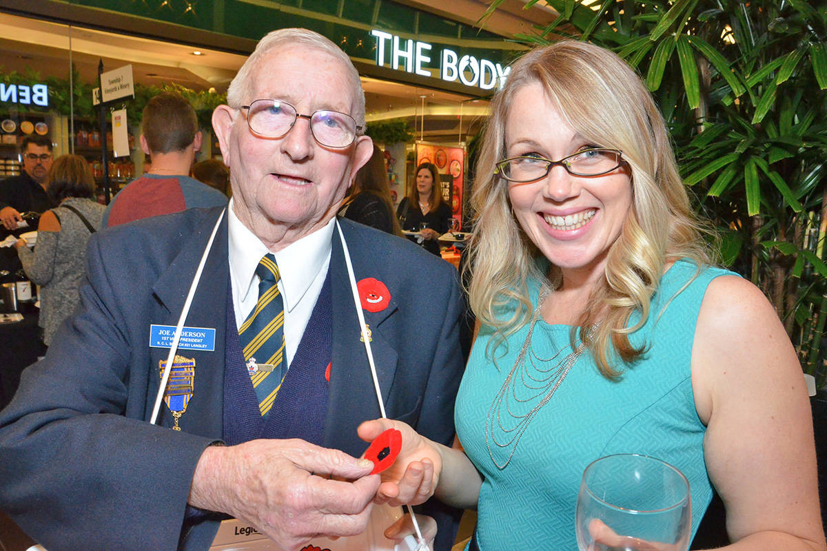 Joe Anderson, with the Royal Canadian Legion Langley branch, attended the Fraser Valley Wine Festival where he was able to receive donations for Remembrance Day poppies. Picking up a poppy was Surrey's Jenna Parker, a first time festival goer. (Heather Colpitts/Langley Advance)