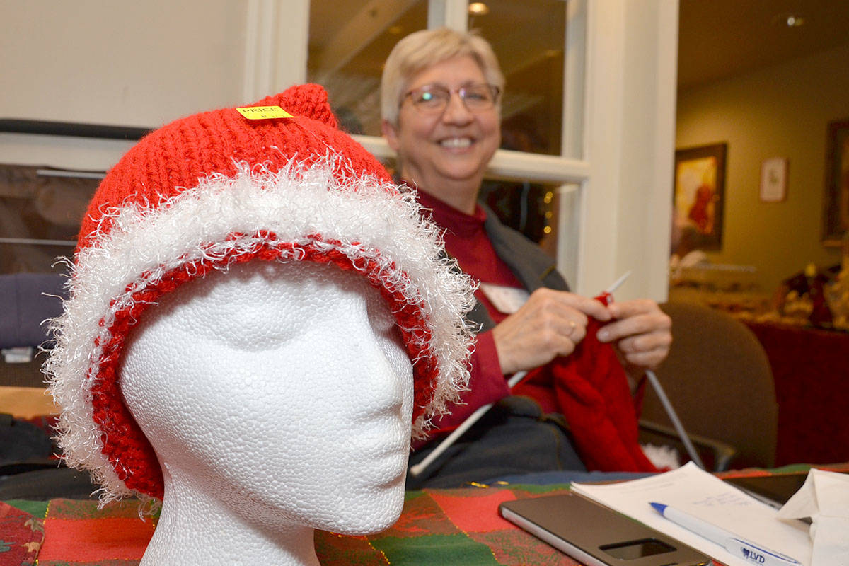 Cheryl Bulycz sold lots of hand-knit Santa hats but is mostly known as the Dryer Ball Lady, another of her crafty items at her booth Nov. 25 at the Langley Seniors Resource Centre Christmas Craft Fair. (Heather Colpitts/Langley Advance)