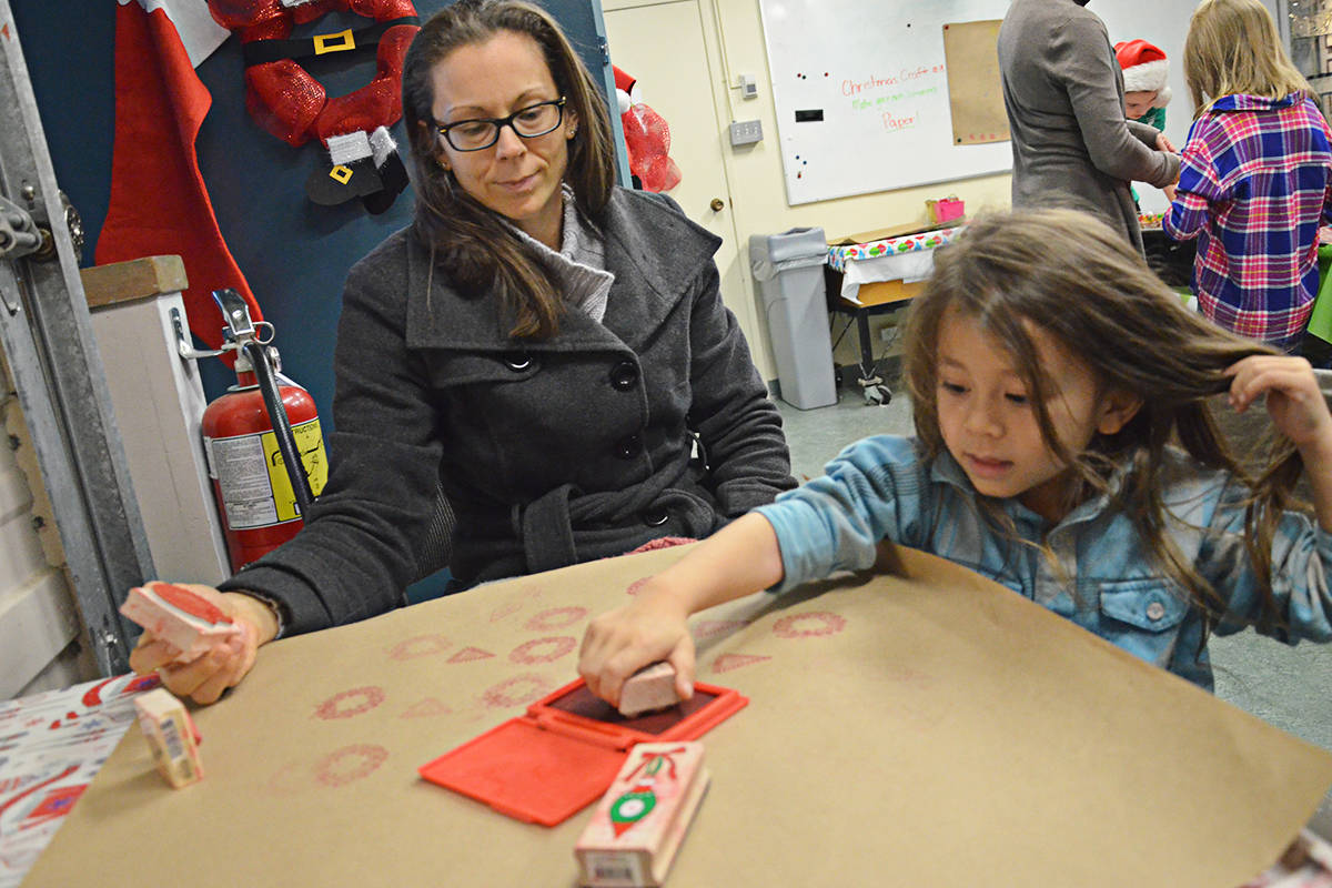 Volunteer Buuchi Mach (left) and Norah Dekker used a pioneer-style wooden toy.