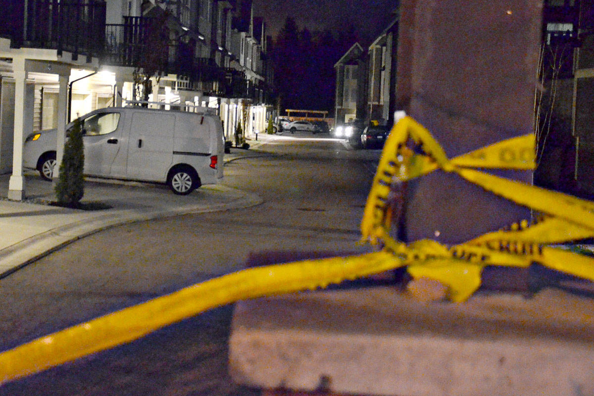 Police tape remains up Friday morning after reports of a fatal shooting in a townhouse complex in Willoughby. (Heather Colpitts/Langley Advance)