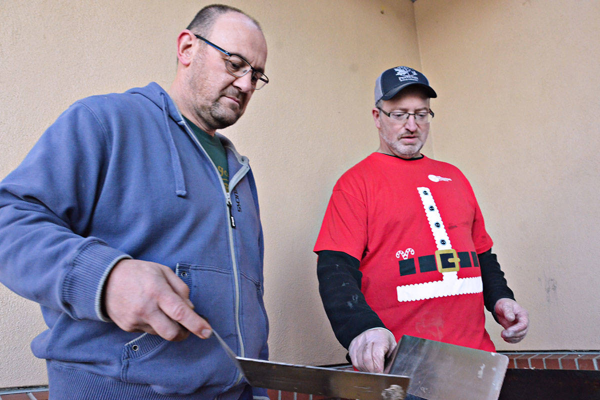 Andy West and Vic Ady (right) were the grill masters for the Santa Breakfast Saturday morning. (Heather Colpitts/Langley Advance)
