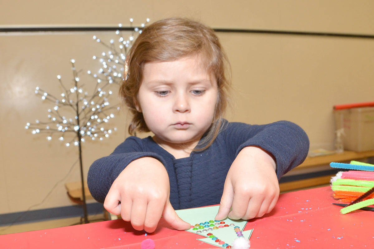 Aliya Screpnek was all business about her Christmas tree crafts at the Willows Church Santa Breakfast Saturday. (Heather Colpitts/Langley Advance)